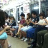 電車の中でスマホをいじる光景